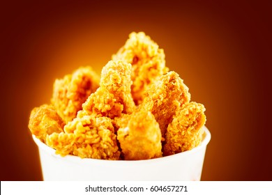 Fried Chicken wings and legs. Bucket full of crispy kentucky fried chicken on brown background