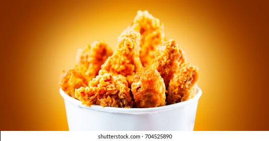 Fried Chicken wings and legs. Bucket full of crispy kentucky fried chicken on brown background. Tasty and juicy deep fried chicken close up