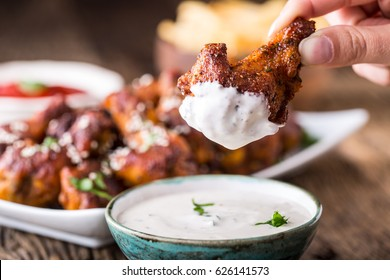 Fried chicken wings on slate board dressing ketchup and potato fries.