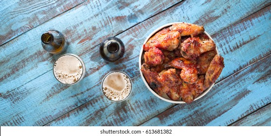 Fried chicken wings in a paper bucket on a wooden table with a beer, top view with a copy space