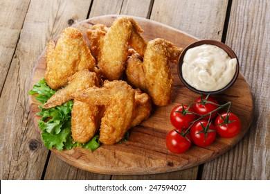 Ailes de poulet sautées avec sauce et tomates