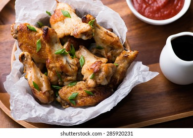 Fried chicken wings with sauces in wooden bowl, top view