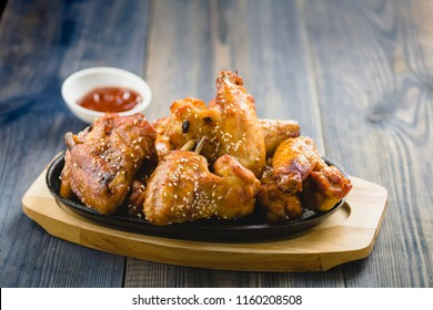 fried chicken wings with sesame on a cast-iron plate
