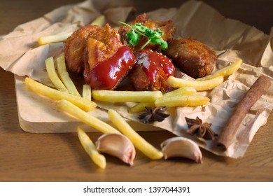 Fried chicken wings with spices and tomato suace or ketchup and french fried on eco brown paper.Delicious fast food and hi trans fat and cholesterol.Concept of trans fat food.