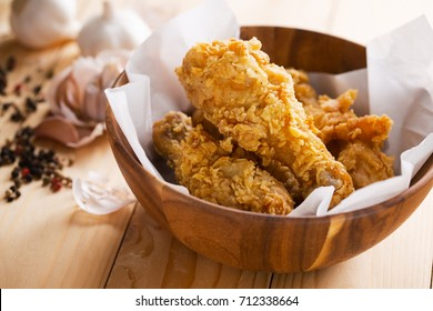 fried chicken in wooden bowl with garlic and pepper ingredient