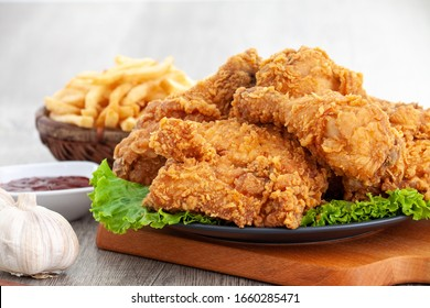 fried chickens, crispy and golden with french fries and sauce on wood table