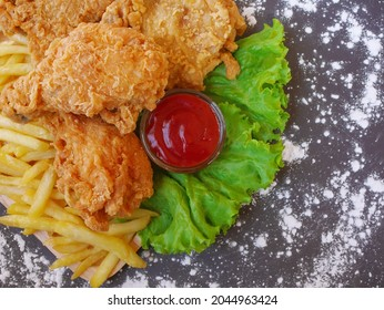 Fried chickens and more frenchfrieds with some ketchup and lettuce on a white background