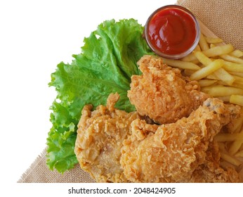 Fried chickens and more frenchfrieds with some ketchup and lettuce on the cutting board