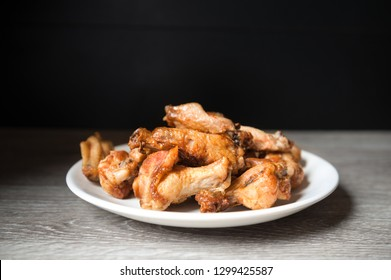 fried chiken wings in the white plate on wooden background