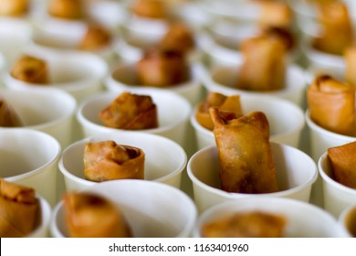 Fried Chinese-Thai style spring rolls in white paper cups. Selective focus.