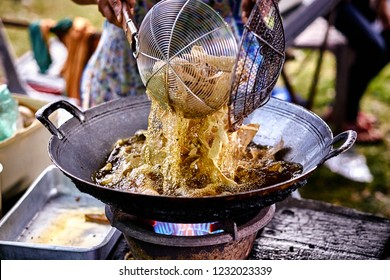 Fried chips in oil at wok. Asian, Indian and Chinese street food. Food court on local market of Langkawi island, Malaysia.Traditional asian street food.