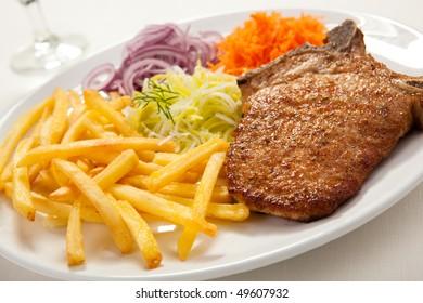 Fried chop pork, chips and vegetable salad