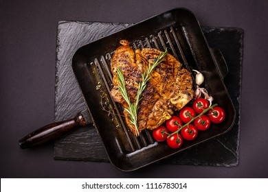 Fried chunk of meat, a beef steak, pork or veal, lamb, lies on a black grill pan, on a black slate. Next to the meat are spices and vegetables. Top view. Copy space