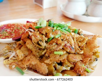 Fried clams.Thai food.Pan-fried crispy mussel with bean sprout.Crispy Fried mussel, flour and egg with spade of frying pan.Popular Thai Cuisine. Delicious food on the sidewalk.
