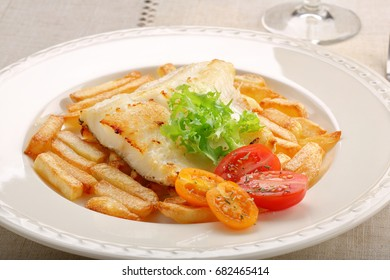 Fried cod fillet on a white plate and french fries