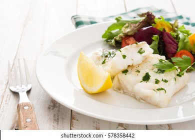 Fried cod fillet and salad in plate on white wooden background