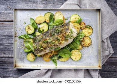 Fried cod fish fillet with vegetable and potatoes as top-view on a tray