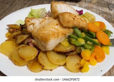 Fried cod with roasted potatoes and stewed vegetables served in a reastaurant in Wismar, North Germany, in the old Baltic harbour
