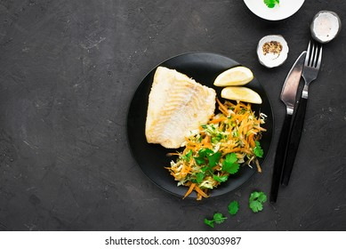 Fried cod with salad from fresh carrots, cabbage, cucumber and dill. Top view. Horizontal