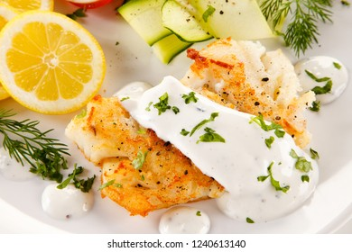 Fried cod and vegetables on white background