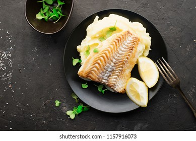 Fried cod white fish with mashed potatoes and lemon slices on a black plate and a dark background. Top View