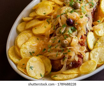 """Fried codfish with onions and sliced potatoes, also known as """"Bacalhau Recheado"""" one of the most famous and typical Portuguese plates."""