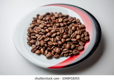 fried coffee beans in a saucer on a white background. Coffee beans as background, isolated on white. Coffee beans on a plate isolated on a white background. coffee beans close-up on a plate.