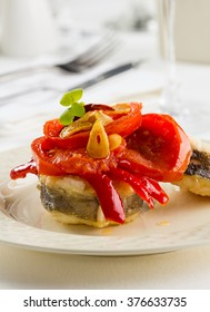 Fried conger with bell pepper, tomato and garlic
