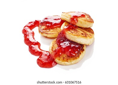 Fried cottage cheese fritters or pancakes with strawberry jam isolated on white background