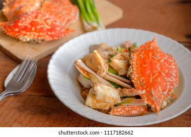 Fried crab with pepper sauce on wooden table