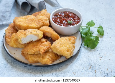 Fried crispy chicken breast nuggets with sauce