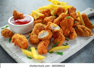 Fried crispy chicken nuggets with french fries and ketchup on white board