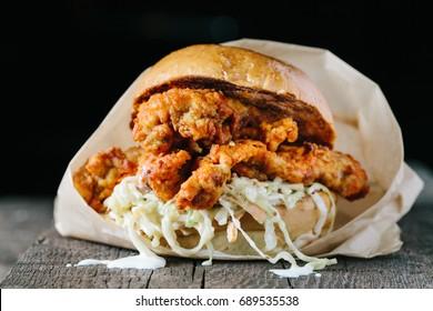 Fried crispy chicken sandwich with coleslaw on dark backgroundhorizontal