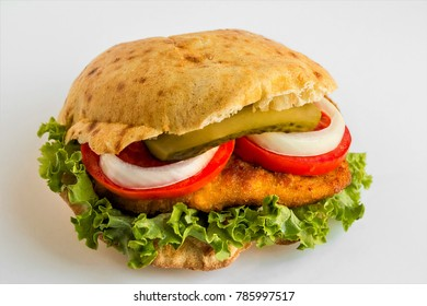 Fried crispy chicken sandwich,tomato,lettuce leaf,onion,cucumber pickle inside.Close up taken,isolated.