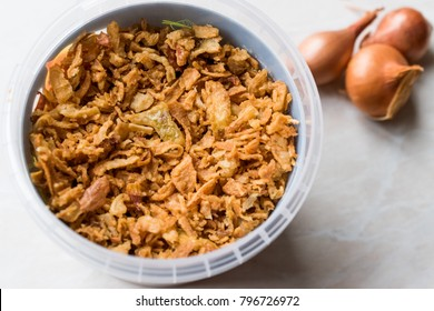 Fried Crispy Onion Flakes in Plastic Package Bowl.