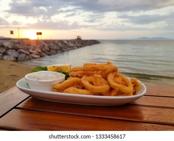 Fried crispy squid rings breaded ( calamari ) with white sauce on sunset with blue sky background.