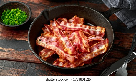 Fried crunchy Streaky Bacon pieces in a cast iron skillet