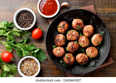 Fried cutlets from minced meat in frying pan and spices on wooden table. Top view, flat lay