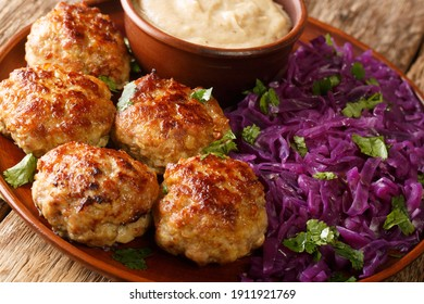 Fried Danish meatballs with hot stewed red cabbage and sauce close-up in a plate on the table.
