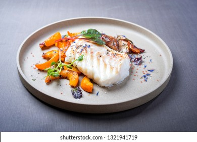 Fried Danish skrei cod fish filet with pumpkin, mushroom and lettuce as closeup on a modern design plate