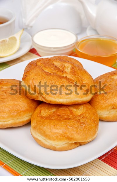 Fried donuts with filling on a white plate with sour cream and jam
