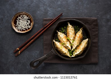 Fried dumplings Gyoza in a frying pan, soy sauce, and chopsticks on a black concrete background, top view