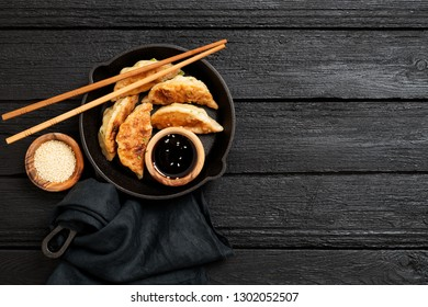 Fried dumplings Gyoza in a frying pan, soy sauce, and chopsticks on a black wooden background, top view
