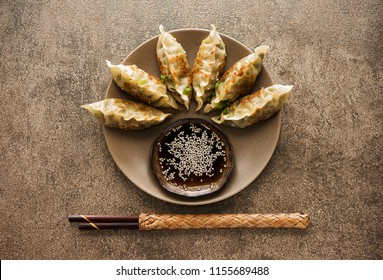 Fried dumplings Gyoza on a plate, soy sauce, and chopsticks on a stone background, top view