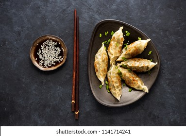Fried dumplings Gyoza in plate, soy sauce, and chopsticks on a black concrete background, top view