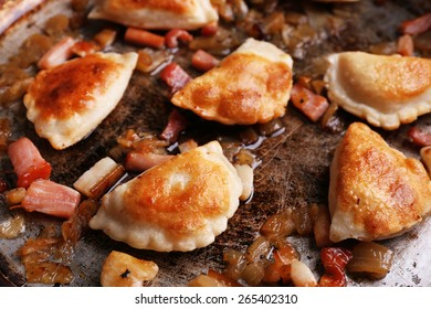 Fried dumplings with onion and bacon in frying pan