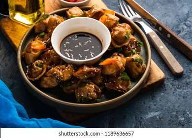 Fried dumplings with soy sauce with pepper and green onions. Asian cuisine.