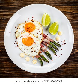 Fried egg with asparagus on white background