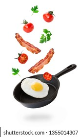Fried egg, bacon and cherry tomatoes flying into iron skillet isolated on white background.