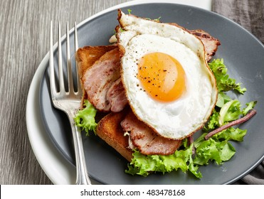 fried egg, bacon and salad on grey plate